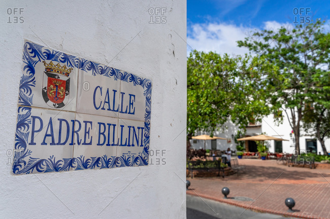 August 13, 2019: Greater Antilles, Dominican Republic, Santo Domingo, Colonial District, Historic street sign on Calle Padre Billini with Parque Billini in the background