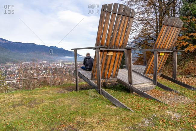November 22, 2019: Europe, Germany, Bavaria, Bavarian Alps, Garmisch-Partenkirchen, man sits on a decorative giant chair and looks down on Garmisch-Partenkirchen