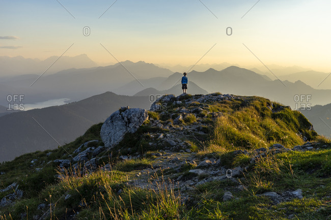 Europe, Germany, Bavaria, Bavarian Alpine foothills, Kochel am See, boy stands on the Benediktenwand and looks at the mountains at sunset