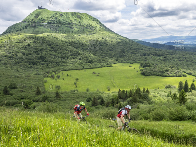 June 27, 2016: Mountain bikers on trail to Puy Pariou, a volcanic peak in the Massif Central in France.