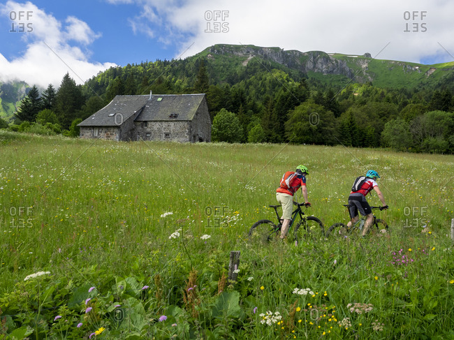 June 28, 2016: Mountain bikers in front of a mountain hut near Montdore in the Massif Central in France.