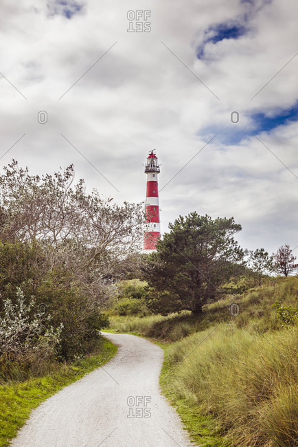 Dune path on the North Sea island of Ameland with a view of the lighthouse
