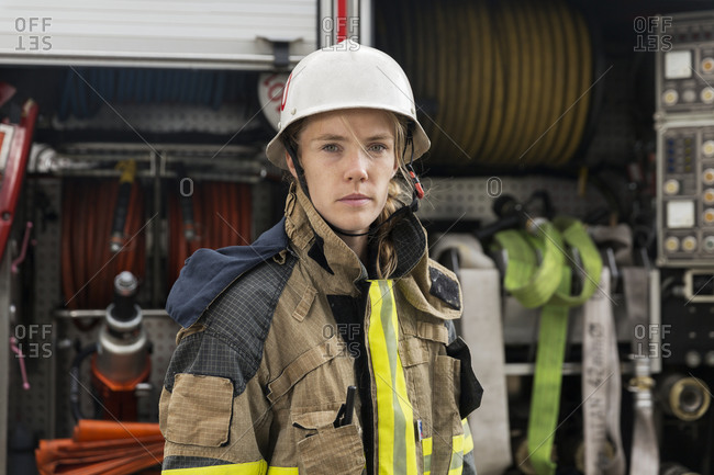 Female firefighter by fire engine