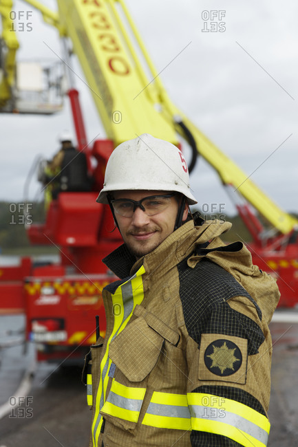 Portrait of young fire-fighter with fire engine on background