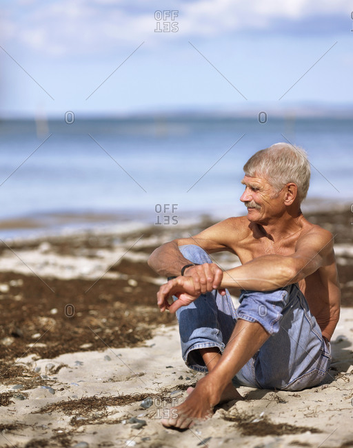 Elderly man in jeans sitting on sandy beach