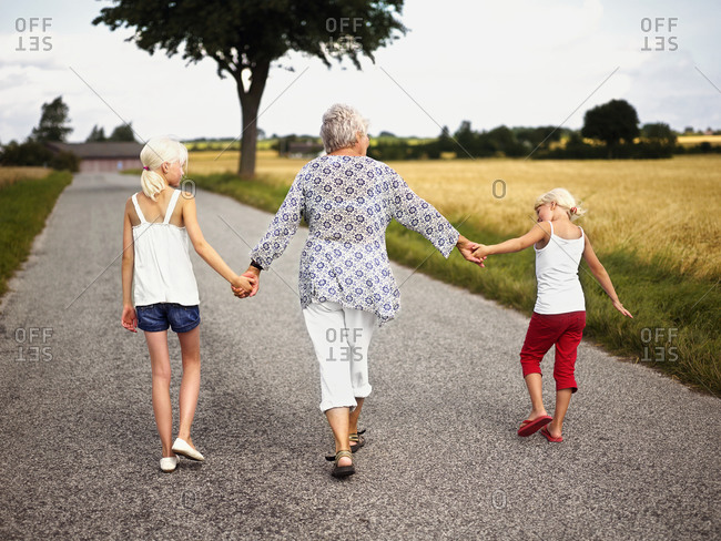 Grandma hand in hand with grandchildren in the countryside