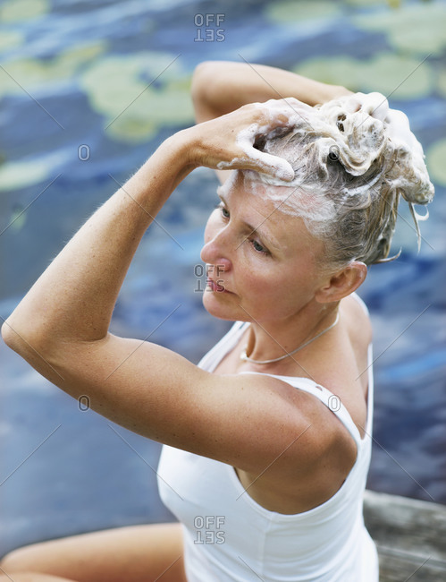 Woman washes her hair by the lake