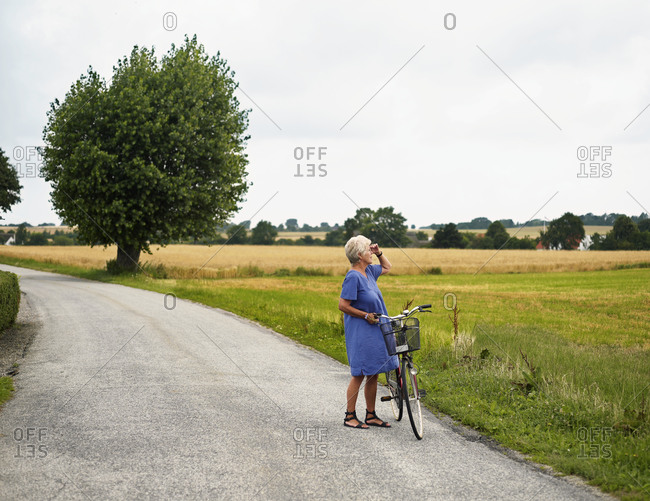 Elderly woman with bicycle by field
