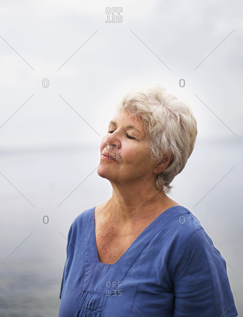 Elderly woman closing her eyes and enjoying the sea