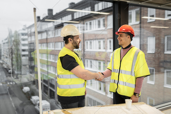 Workers having handshake at construction site
