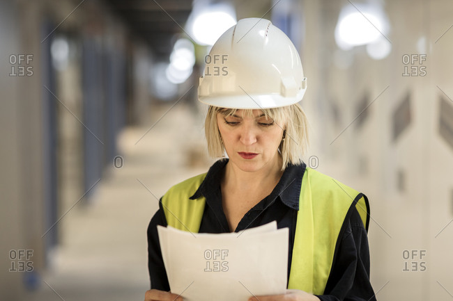 Female worker reading documents on site