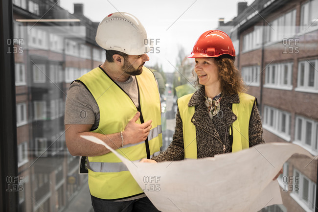 Workers reviewing blueprint at construction site