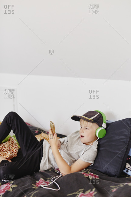 Boy with headphones looking at cell phone