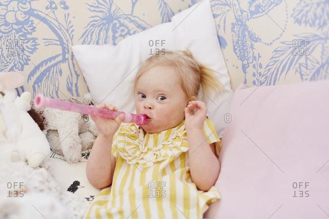 Girl holding flute in bedroom