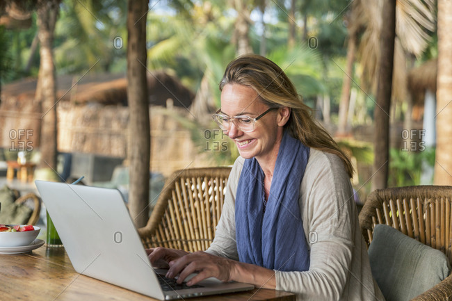 Woman in outdoor cafe using laptop