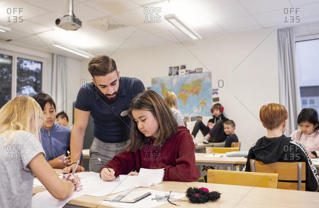 Teacher helping girl in classroom