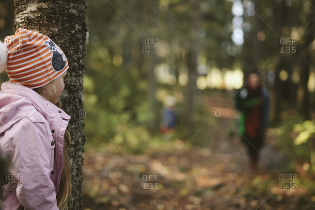 Girl playing hide and seek in forest