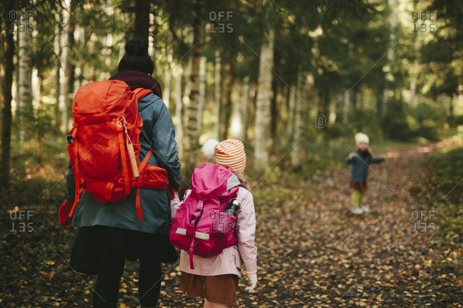 Mother with daughter walking through forest