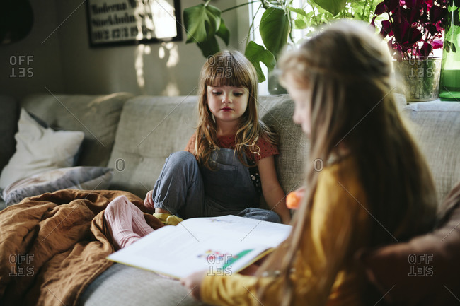 Sisters reading book on sofa