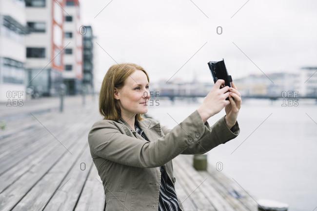 Woman taking selfie by a waterfront