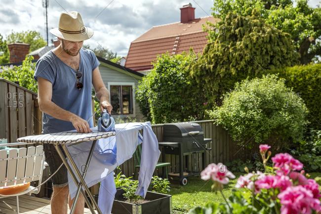Man ironing clothes in garden