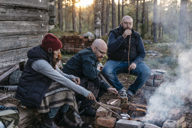 People preparing sausages over log fire