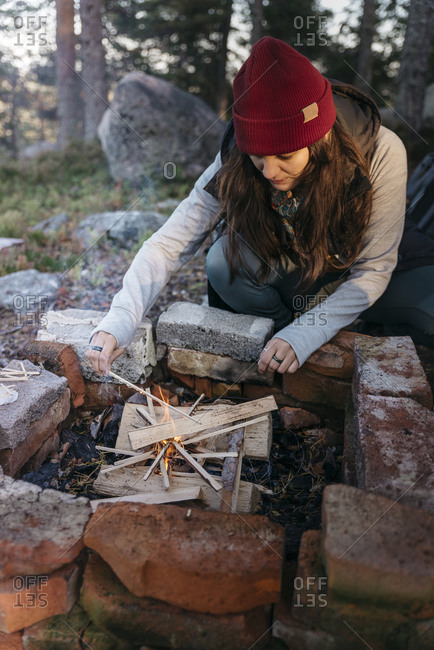 Woman making campfire with wood