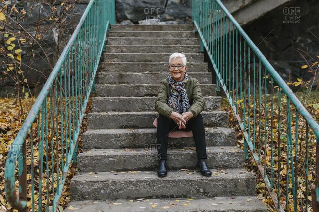 Senior woman sitting on stairs