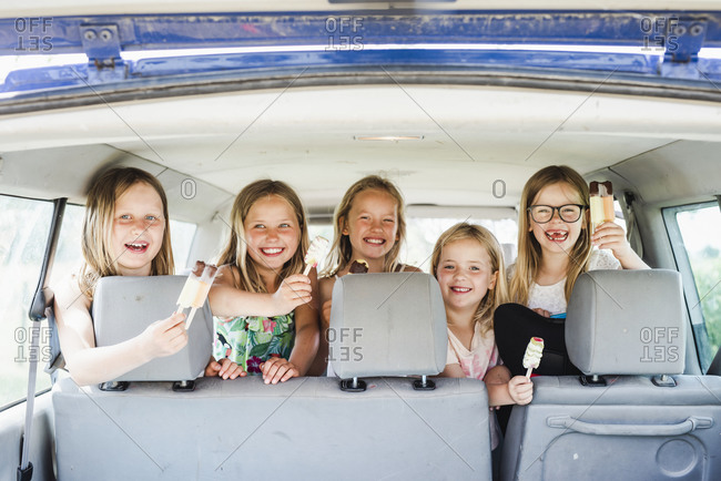 Happy girls in car holding ice cream bars
