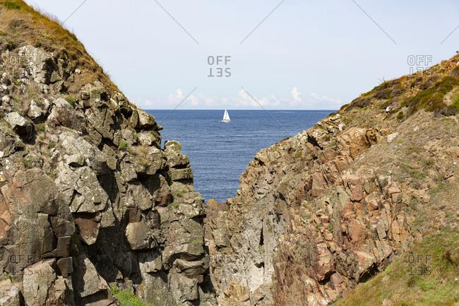 Sailboat seen through rocky cliff