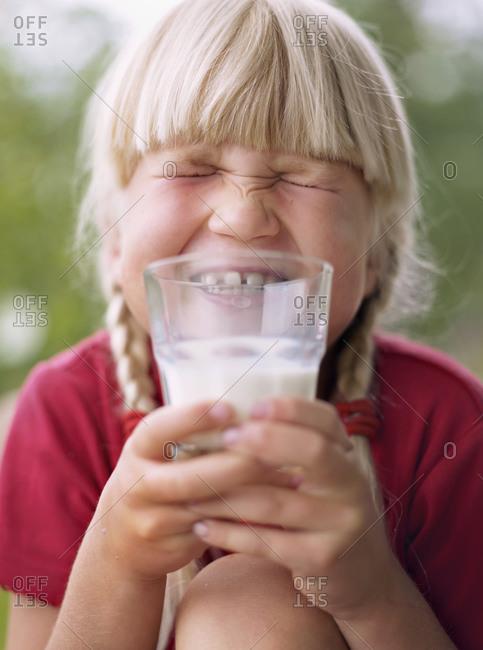 Smiling girl holding glass of milk