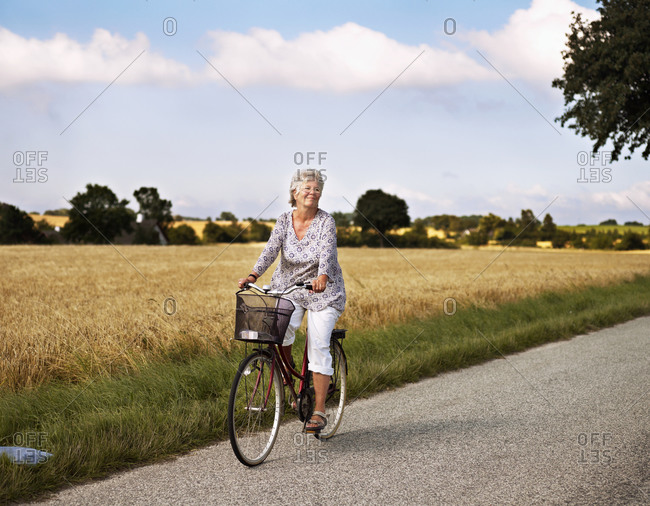 Woman cycling on rural road