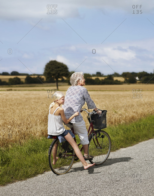Grandmother cycling with her granddaughter