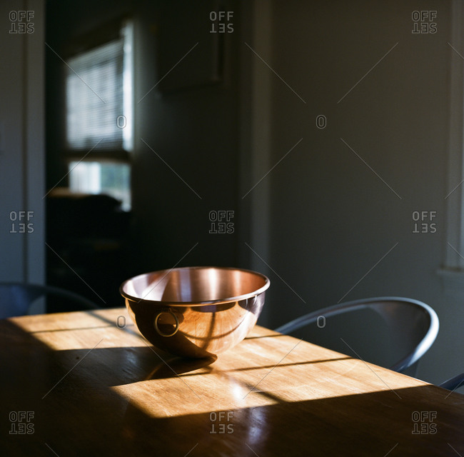 A copper bowl on a table in the sunlight