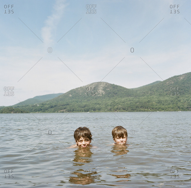 Two young boys swimming in a lake