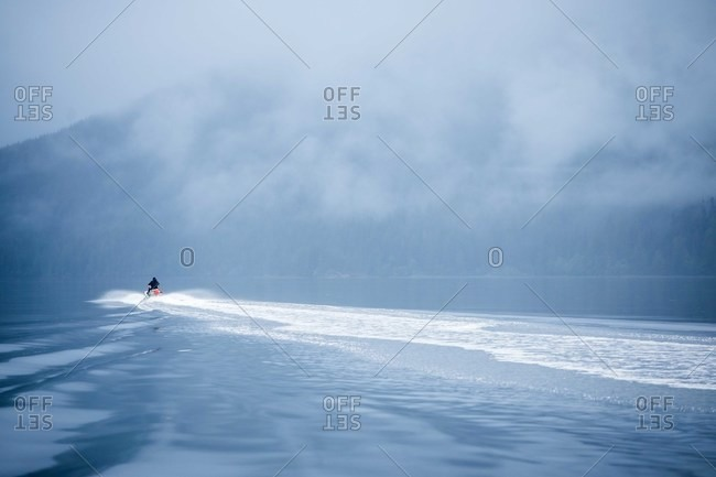Person riding personal watercraft vehicle in the ocean by fog covered mountain