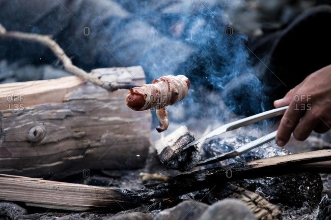 Hot dog wrapped in bacon being cooked over a campfire