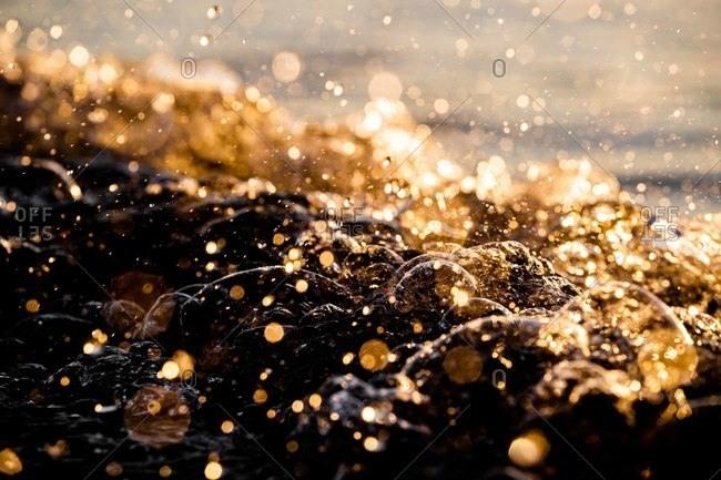 Splashing waves in the ocean at sunset