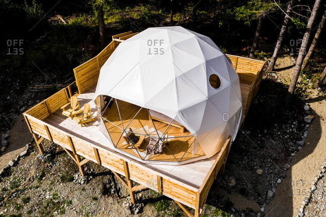 Dome tent on wooden platform in the mountains