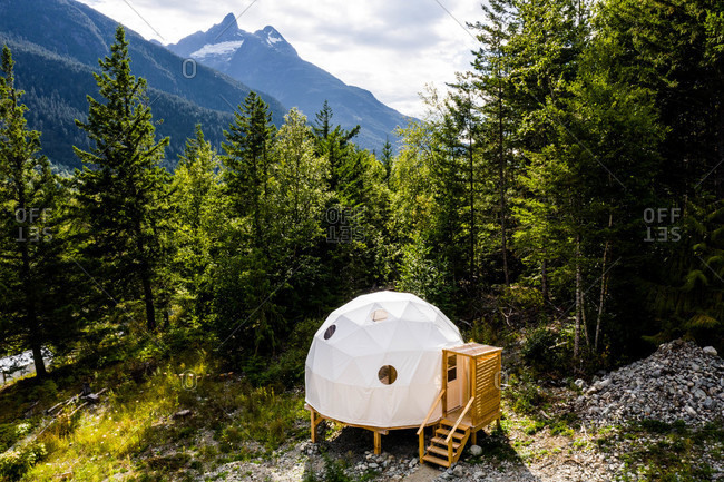 Dome tent on wooden platform in the forest