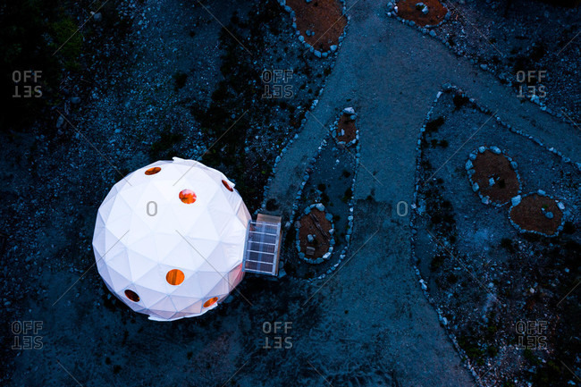 Aerial view of a white dome tent in the mountains at night