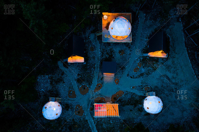 Aerial view of a campsite with a-frame cabins and dome tents in the mountains at night