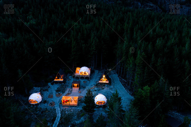 A campsite with a-frame cabins and dome tents in the mountains at night