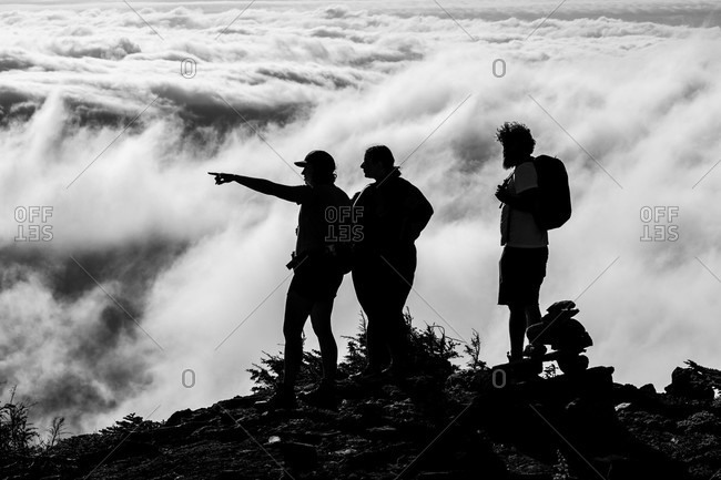 Canada - August 17, 2020: Three hikers standing on a mountain peak pointing out over the clouds