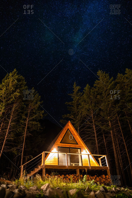 An a-frame cabin in the mountains at night