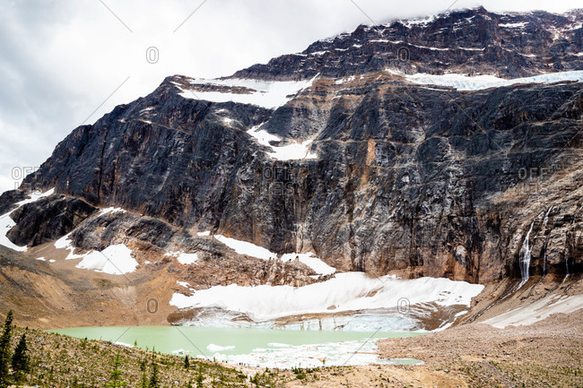 Small blue lake in the mountains with snow