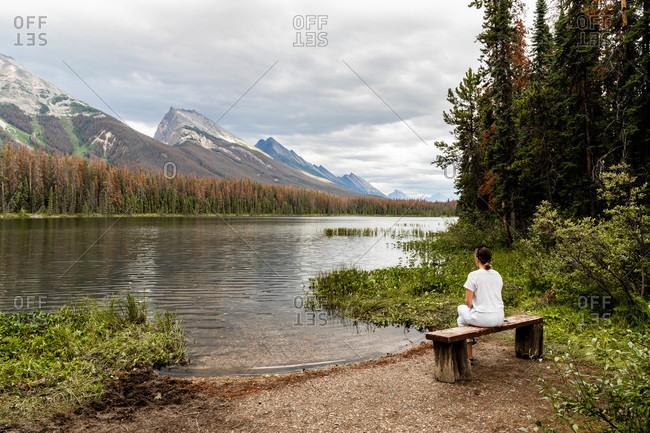 Woman sitting on rustic bench overlooking mountainside lake