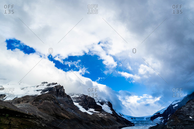 Snow covered mountaintops under clouds skies