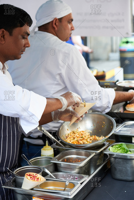 London, United Kingdom - July 23rd 2016: Two chefs serve Indian street food at a market stall