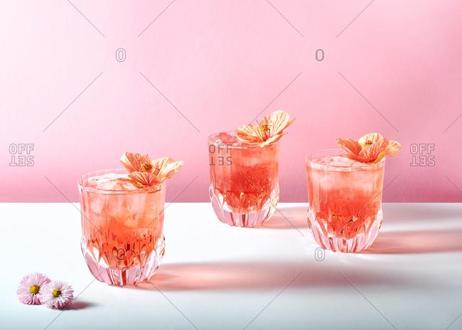 Blood orange cocktails served in vintage glasses with edible flower garnishes